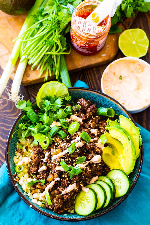 Overhead of Korean Beef Bowl with fresh ingredients and sriracha sauce sorrounding it.