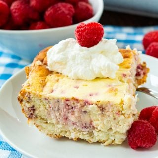 Raspberry Cheesecake Bar on a plate with whipped cream and fresh raspberries