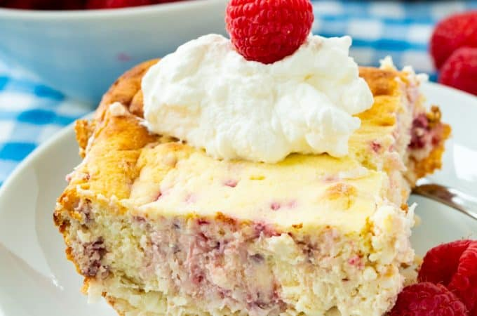 Raspberry Cheesecake Bar on a plate with whipped cream and fresh raspberries