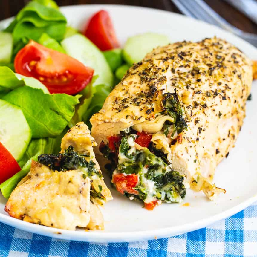 Chicken stuffed with Spinach and Srtichokes on a white plate with salad.