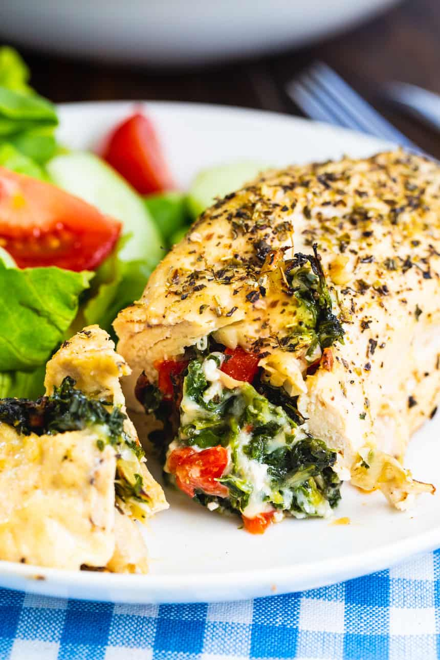 Spinach and Artichoke Stuffed Chicken on a white plate .
