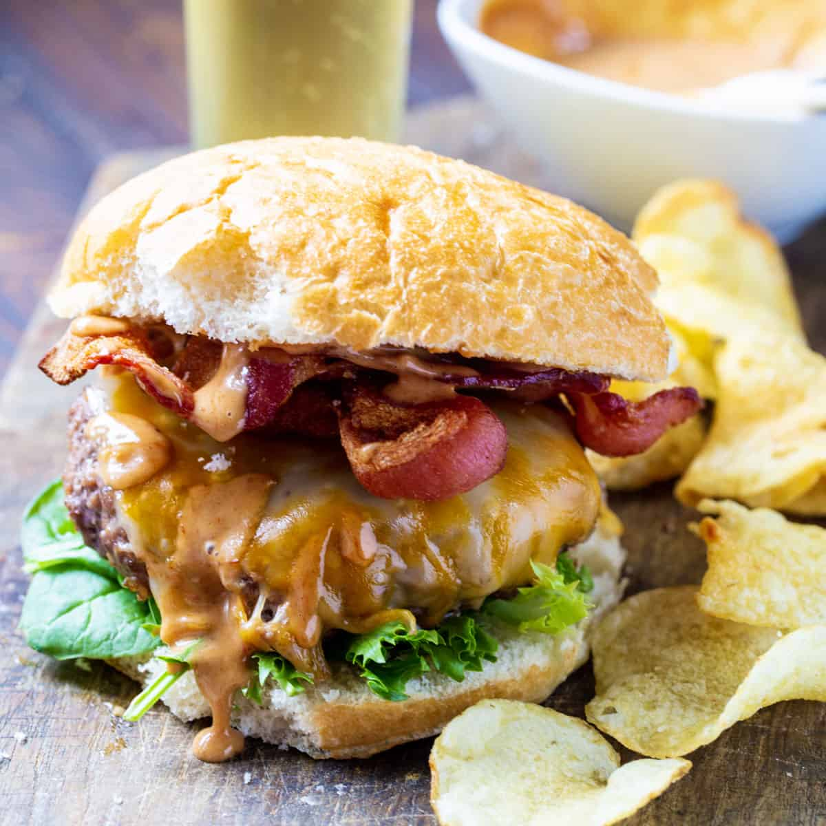 Burger on a bun surrounded by chips.