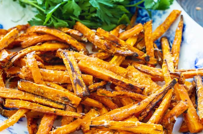 Carrot Fries on a serving plate with parsley.