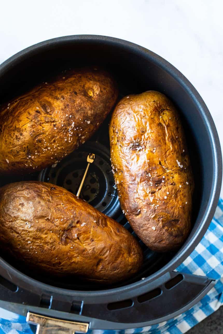 Three baked potatoes in an air fryer basket.