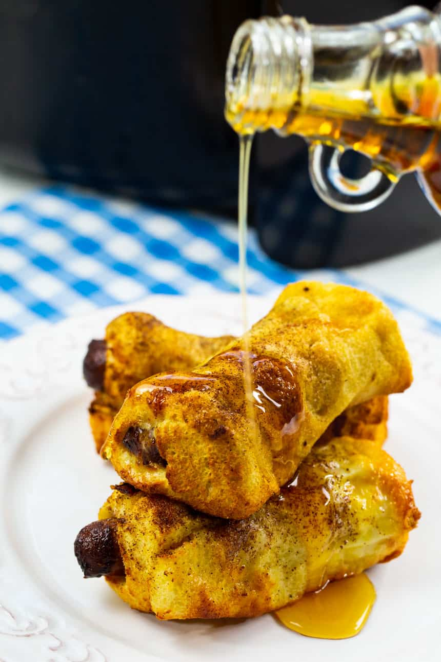 Drizzling maple syrup on Air Fryer French Toast Sausage Roll-Ups .