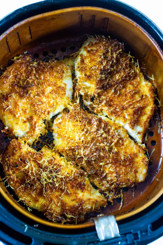 Parmesan Chicken in an air fryer basket.