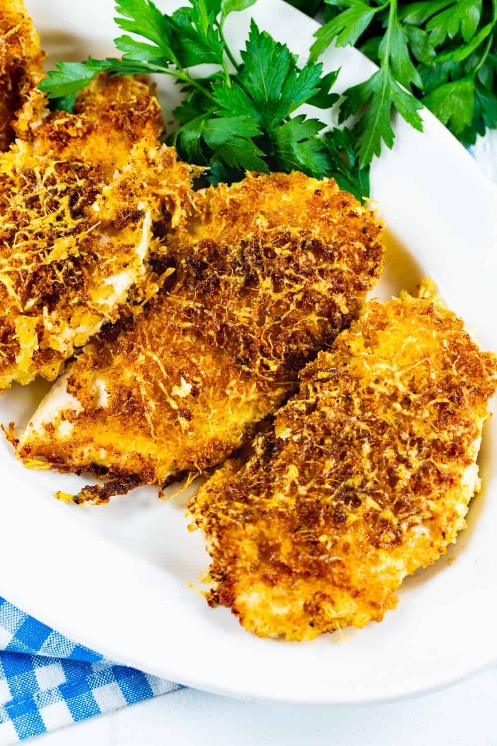Parmesan Crusted Chicken on serving platter with parsley.
