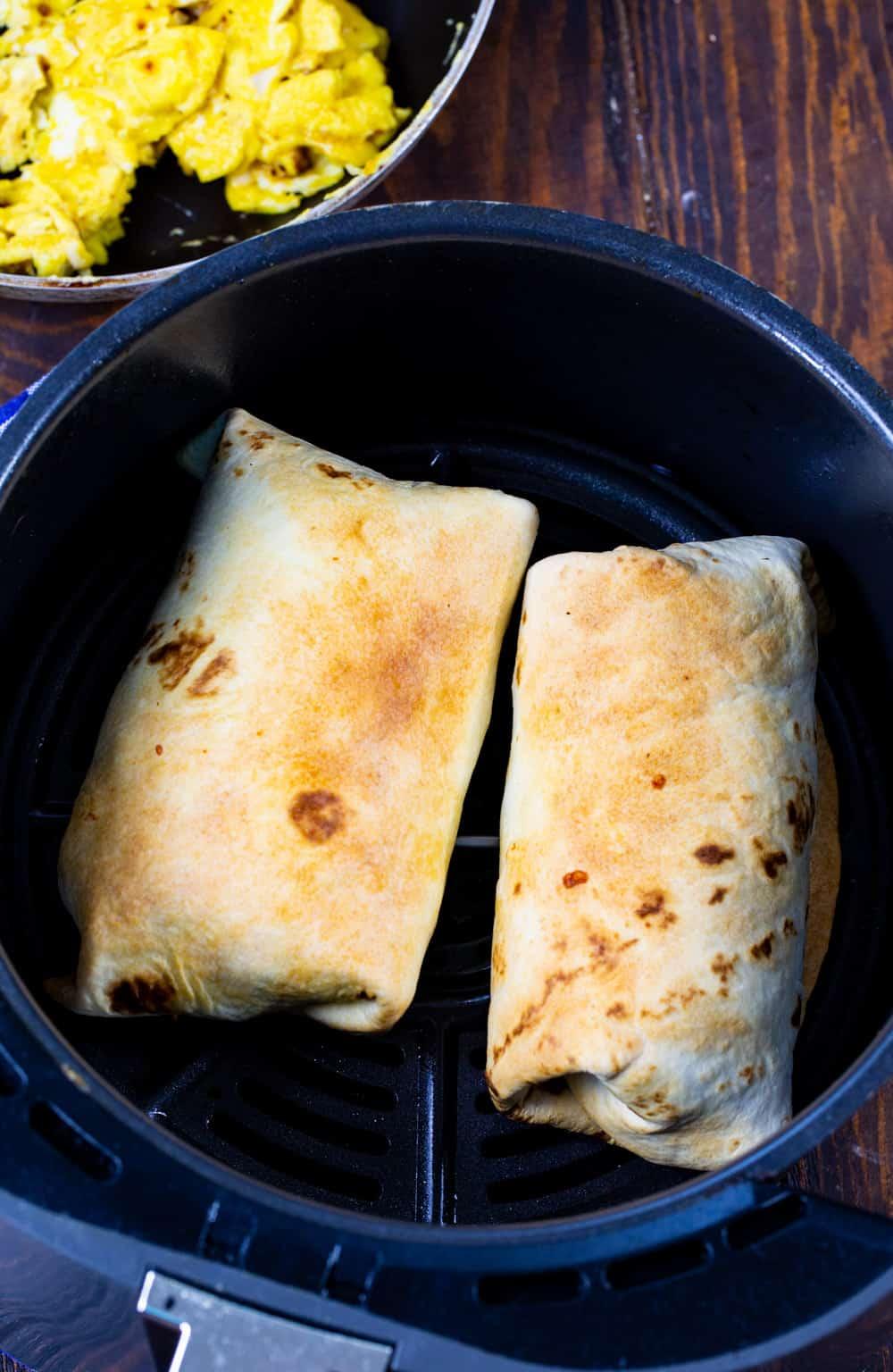 Two Breakfast Burritos in air fryer.