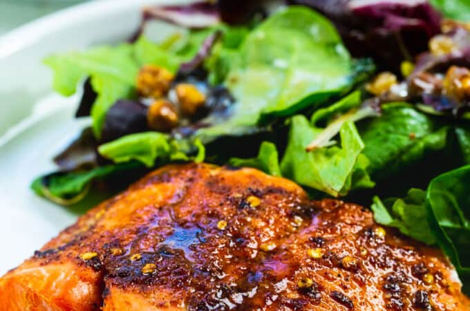 Air fried salmon on a plate with salad.