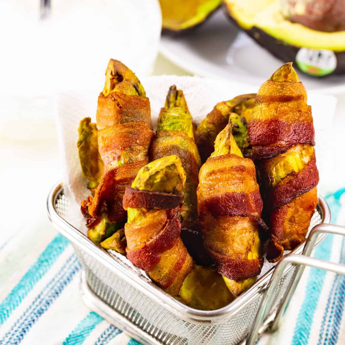 Air Fryer Bacon Wrapped Avocado Fries in a small metal basket.