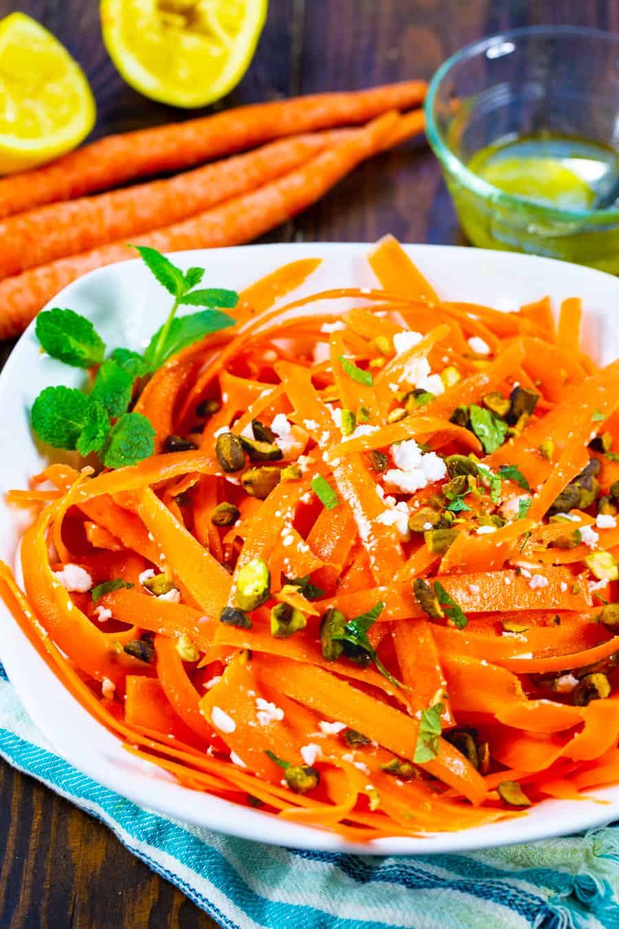 Carrot salad in a bowl with whole carrots and lemons in background.