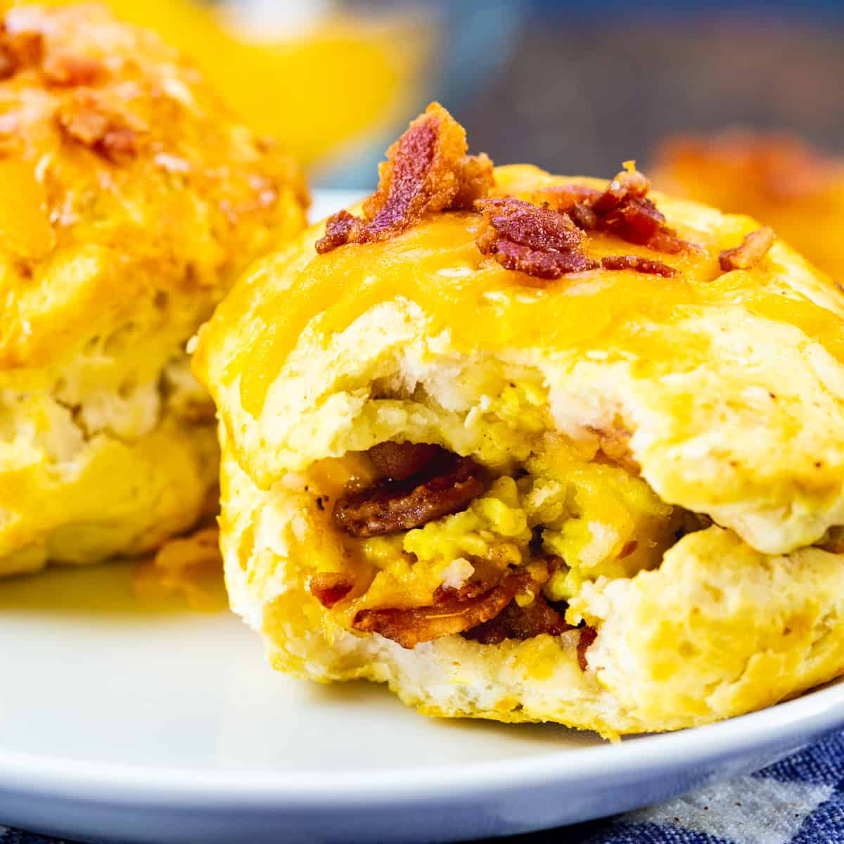 Air Fryer Bacon Egg & Cheese Biscuits Bombs with bite bitten to show inside.