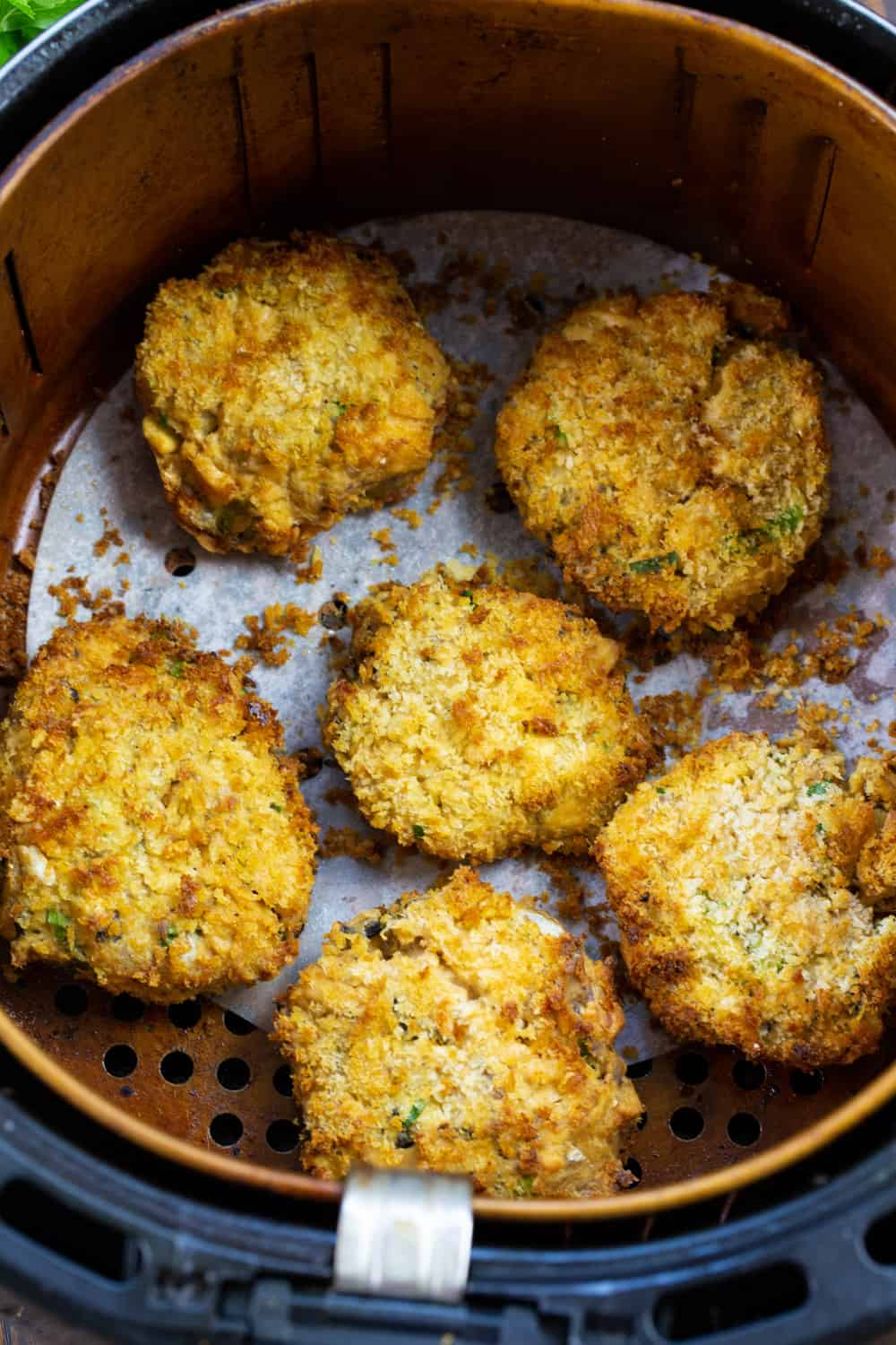 Cooked salmon patties in an air fryer basket.