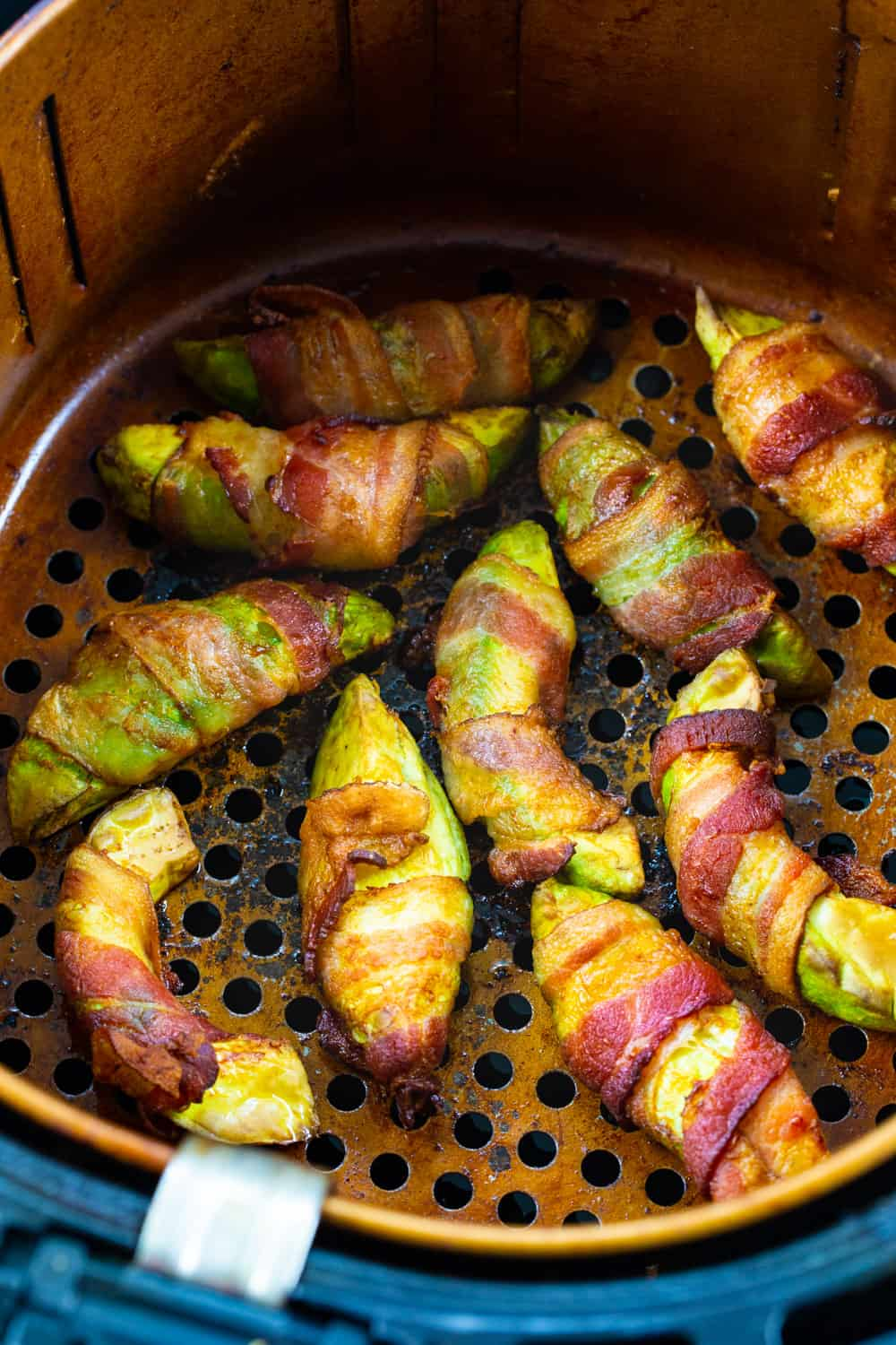 Bacon Wrapped Avocado Slices in air fryer basket.