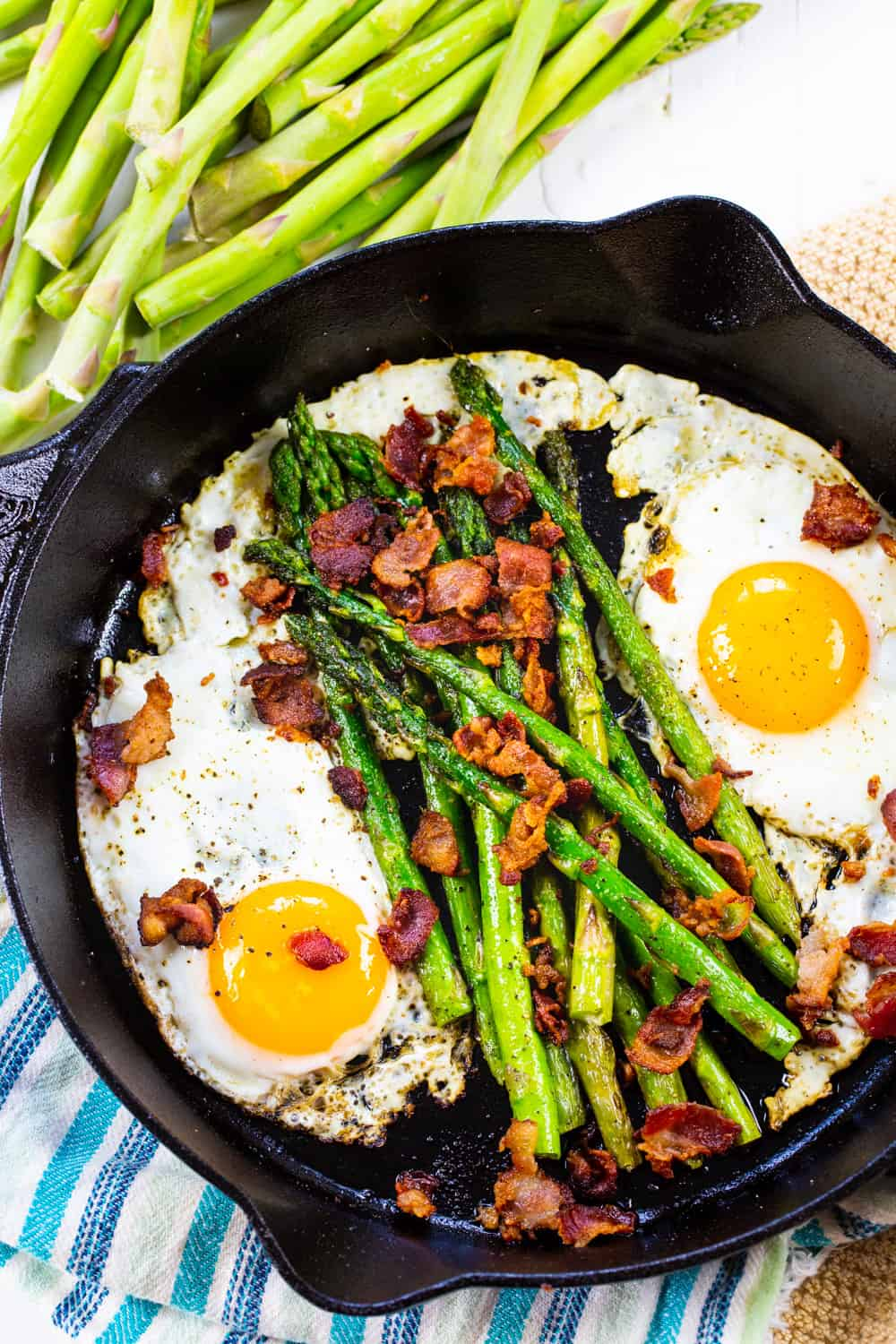Two fried eggs, asparagus spears, and crumbled bacon in a cast iron pan.
